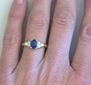 Dark blue natural sapphire ring with side diamonds in 14k yellow gold